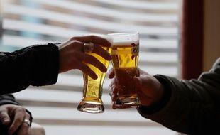 Deux hommes en train de trinquer dans un bar (image d'illustration).