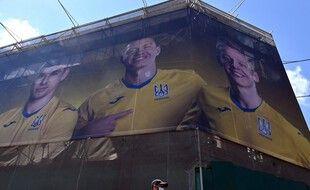 Des passants devant un panneau représentant des joueurs de l'équipe de football ukrainienne, à Kiev, le 7 juin 2021.