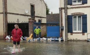 Face à la montée des eaux, les habitants tentent de protéger leur habitation.