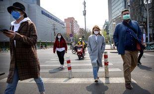 Des passants dans la rue à Pékin, le 7 avril 2020.