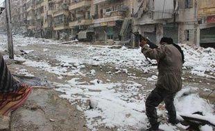 Alep, le 11 décembre 2013, un opposant au régime syrien pointe son arme vers les balcons enneigés de la ville.