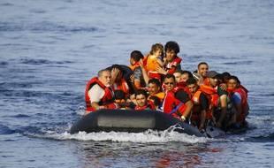 Des migrants à bord d'un canot pneumatique en provenance de la Turquie, approchent des côtes de l'île grecque de Lesbos, le 9 septembre 2015.