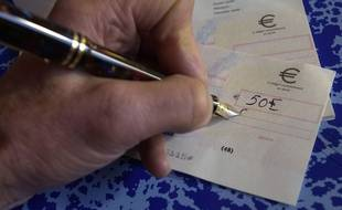 Une personne qui signe un chèque (Illustration).