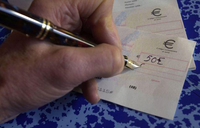 Une personne signe un chèque (Illustration).