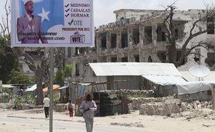 Un homme passe devant une affiche de campagne du président Sheikh Sharif Ahmed, à Mogadicio, le 9 septembre 2012.