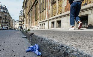 Un masque jeté dans une rue de Paris. (Illustration)