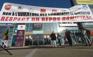 Des syndicalistes manifestent contre l'ouverture dominicale du supermarché Carrefour Grand Maine à Angers.