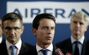 Le Premier ministre Manuel Valls (c) en conférence de presse au côté du DRH adjoint d'Air France Xavier Broseta (g) et du directeur long-courriers Pierre Plissonnier (d) le 6 octobre 2015 à Roissy-en-France