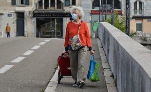 Une femme porte un masque à Grenoble pour aller faire ses courses.