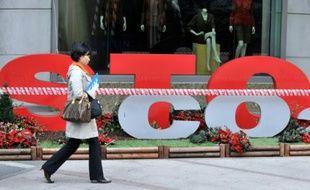 """Une femme passe devant un slogan """"Stop CO2"""" à Séoul le 9 décembre 2009"""