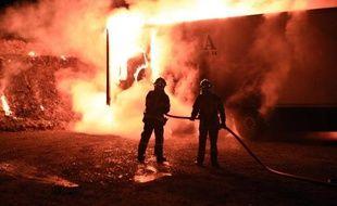 Des pompiers éteignent un incendie provoqué par des producteurs de porcs français qui ont mis le feu à une remorque d'un camion espagnol transportant de la viande en provenance de ce pays, le 8 mars 2015 à Landivisiau, dans le Finistère