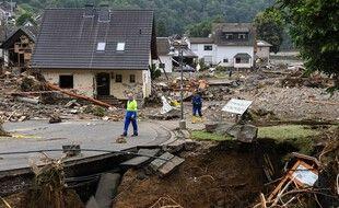 Deux hommes marchent sur une portion de route partiellement effondrée parmi des maisons détruites après les intempéries et inondations à Schuld, en Allemagne, le 16 juillet 2021.