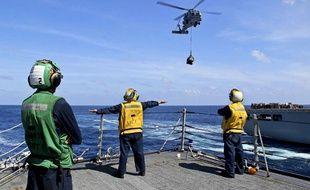Des marins de la US Navy lors d'une opéation de recherche du vol MH370, le 18 mars 2014.