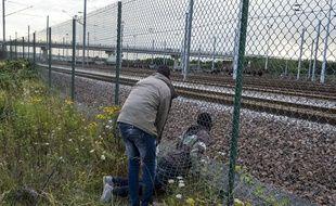 Deux migrants franchissent une barrière pour s'introduire dans le site d'Eurotunnel, près de Calais.