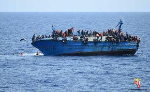 Photo fournie le 25 mai 2016 par la Marine italienne montrant un bateau de migrants sur le point de faire naufrage au large de la côte libyenne