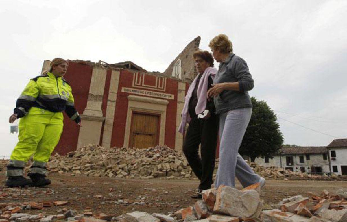 Des habitants passent devant l'église San Martino à Cento dans le nord de l'Italie, où la terre a tremble le 20 mai 2012. – AP Photo/Luca Bruno/SIPA