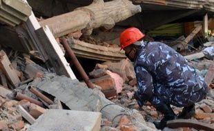 Un secouriste à la recherche de survivants, au milieu des décombres le 12 mai 2015 à Katmandou