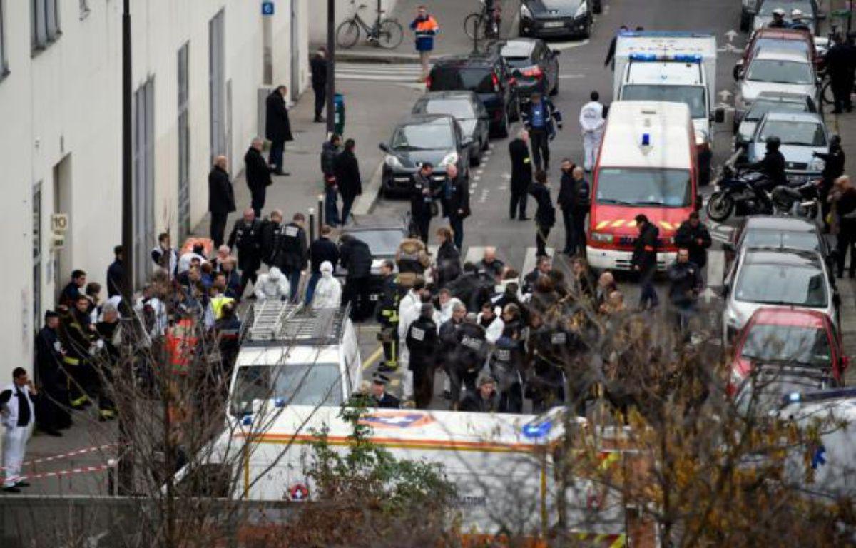Des pompiers, des officiers de police et des médecins légistes devant le siège de Charlie hebdo après les attaques le 7 janvier 2015 – MARTIN BUREAU AFP