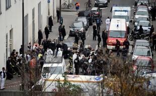 Des pompiers, des officiers de police et des médecins légistes devant le siège de Charlie hebdo après les attaques le 7 janvier 2015