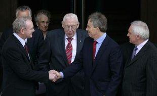 Le Premier ministre britannique Tony Blair serre la main au catholique Martin McGuinnes, investi vice-Premier ministre de l'Irlande du Nord. Derrière eux, le protestant Ian Paisley, nommé Premier ministre le 8 mai 2007.