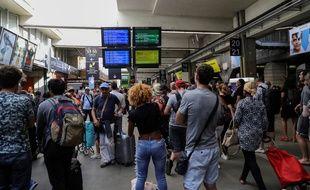 Des passagers rassemblés devant le point d'information de la SNCF, après une panne à la gare Montparnasse à Paris, le 18 août 2018.