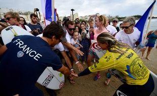 La championne (en jaune) a été accueillie triomphalement sur la plage par la délégation française.