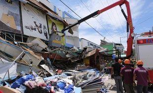 Des sauveteurs inspectent un bâtiment effondré à Digos, dans le sud des Philippines, le 31 octobre 2019.