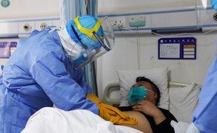 Photo prise le 28 janvier 2020 montrant un membre du corps médical auscultant un patient, dans un hôpital de Zouping en Chine.