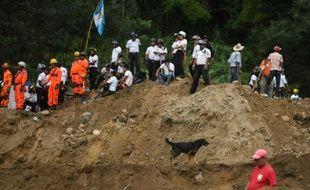 Des secouristes, pompiers et habitants sur les lieux d'un glissement de terrain à Santa Catarina Pinula, à 15 km à l'est de Guatemala, le 2 octobre 2015