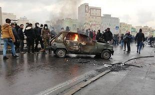 Des manifestants iraniens se rassemblent autour d'une voiture en flammes lors d'une manifestation contre l'augmentation du prix de l'essence dans la capitale, Téhéran, le 16 novembre 2019.