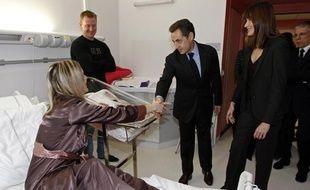 Le chef de l'Etat Nicolas Sarkozy (C) et sa femme,  Carla Bruni-Sarkozy (D), visitent le service de maternité de l'hôpital Henri Duffaut à Avignon, le 21 décembre 2010.