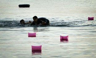 Des migrants syriens nagent vers une plage de l'île de Kos, après avoir effectué la traversée depuis les côtes turques sur un pneumatique surchargé, le 15 août 2015