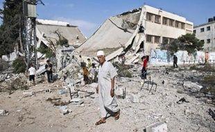 Un Palestinien marche devant les ruines d'une école détruite par les bombardements à Gaza le 26 août 2014