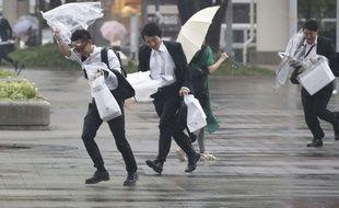 Des employés de bureau courent sous la pluie à l'approche du typhon, à Kanagawa, près de Tokyo, le 28 juillet 2018.