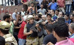 Un soldat pointe son arme sur la foule de manifestants, devant la mosquée Al-Fath, au Caire, le 17 août 2013