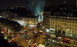 FRANCE, Paris : Les pompiers s'affairent autour du garage en flammes rue Riquet à Paris, le 16 novembre 2007. Deux pompiers sont ensevelis sous un mur qui s'est effondré lors du sinistre dû à l'explosion d'un véhicule.