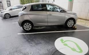 Une voiture électrique en charge sur une place de parking dédié à Paris.