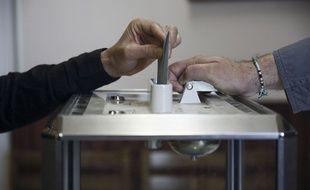 Le dépôt d'un bulletin de vote dans une urne.