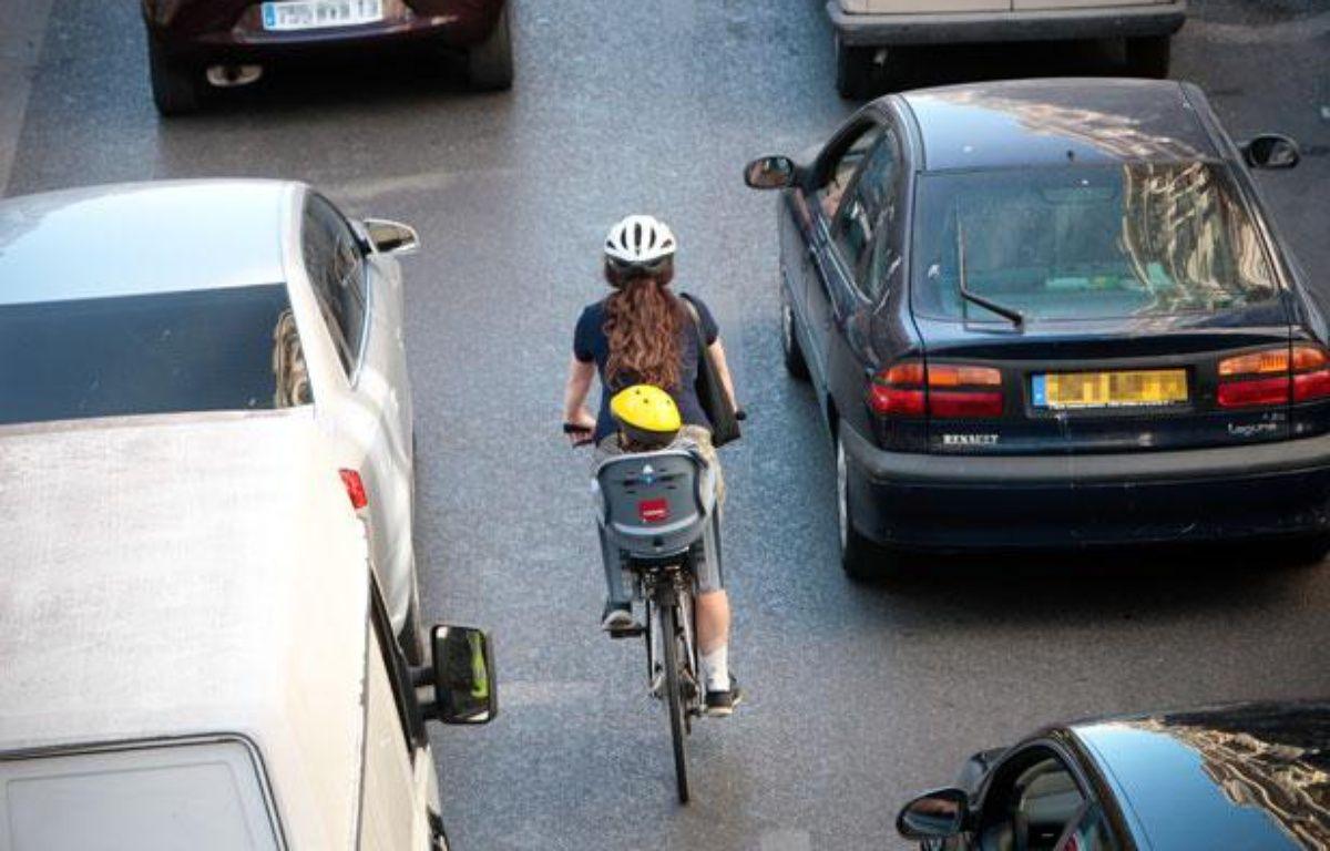 Une femme sur un vélo, avec un porte bébé, dans la circulation. Casque. – PATRICE MAGNIEN / 20 MINUTES