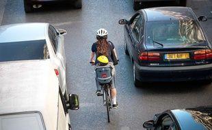 Une femme sur un vélo, avec un porte bébé, dans la circulation. Casque.