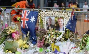 Portraits de Katrina Dawson (g) et Tori Johnson, tués lors de la prise d'otages dans un café à Sydney, au milieu de fleurs sur le site en hommage aux victimes, à Sydney, le 23 décembre 2014