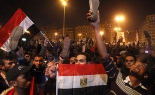 Les manifestants égyptiens brandissent leurs chaussures, alors qu'Hosni Moubarak s'exprime, pour montrer leur désapprobation place Tahrir, le 10 février 2011.