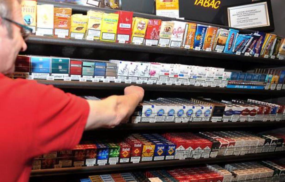 Un buraliste devant ses rayons de paquets de cigarette – Philippe Huguen AFP