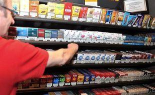 Un buraliste devant ses rayons de paquets de cigarette