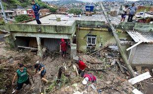 Des habitants d'Ibirite (Brésil) nettoient la boue et les débris après le passage d'une tempête, le 25 janvier 2020.