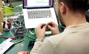 Illustration d'un homme réparant un ordinateur.