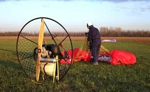 Pilote de paramoteur pliant son parachute apres l'atterrissage ( illustration )
