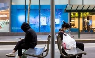 Des passagers attendent le tram à Melbourne, le 3 août 2020.