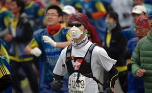 Un participant au marathon de Pékin portant un masque anti-pollution, le 19 octobre 2014 en Chine.