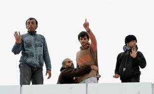 Des réfugiés syriens installés sur le toit d'un bâtiment sur le port de Calais le 4 octobre 2013